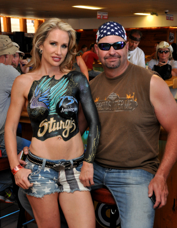body painted blonde woman with a blue themed sturgis logo on her chest standing next to a man