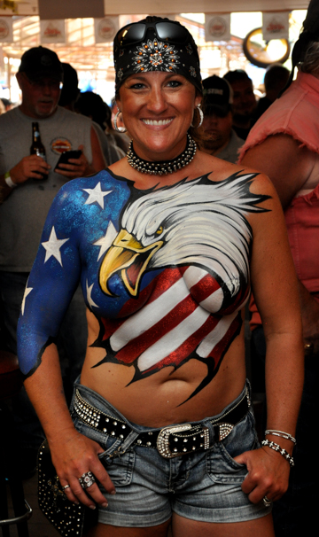 body painted woman with a united states flag themed log on her chest that features a bald eagle head