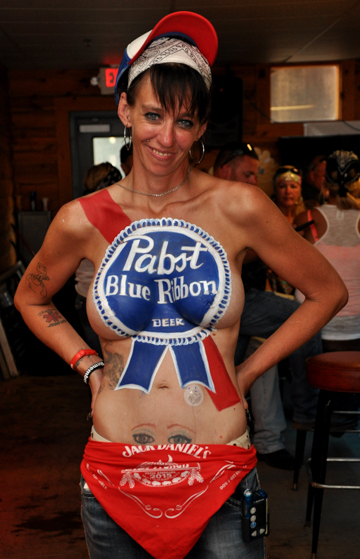 body painted black haired woman with a detailed pabst blue ribbon logo on her chest