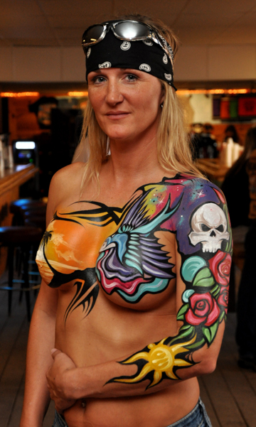 body painted blonde woman with a brightly colored painting on her chest and left arm featuring skulls and roses
