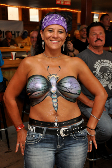 body painted black haired woman with a blue and black butterfly painted on her chest that has a cartoon feel