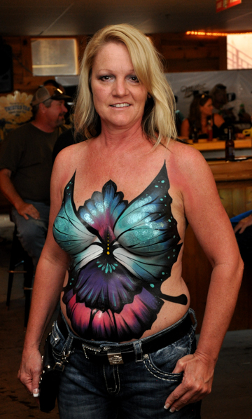 body painted blonde woman with a colorful butterfly themed logo on her chest and stomach