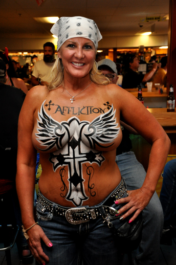 body painted blonde woman with a winged affliction logo in black and white on her chest