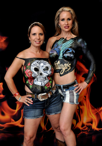 two women with body paintings on their chests one with a skull and roses and the other with a sturgis logo in blue and gold on a black background