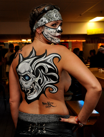 brunette woman with a skull jaw face painting looking over her shoulder and showing a detailed black and white skull body painting on her back