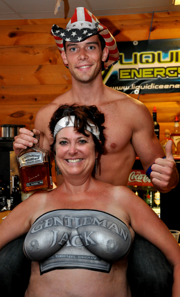 woman body painted with a gentleman jack logo on her chest with a man behind her wearing an american flag themed cowboy hat