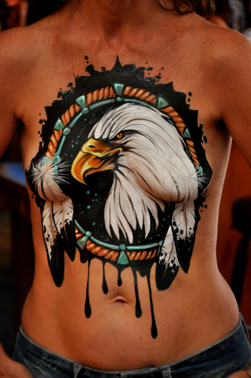chest of a woman with a detailed body painting that resembles a dream catcher and has a bald eagle in the middle of it