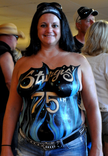 black haired woman with a 75th sturgis logo painted on her chest in blue on a black background