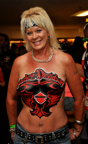 blonde woman with a black and orange harley davidson logo painted on her chest