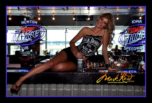 blonde woman sitting on a bar with a jack daniels logo painted on her chest