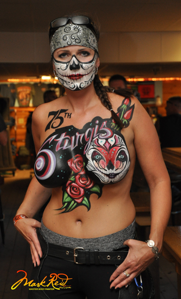 brunette woman with a skull jaw face painting and a sturgis 75th anniversary body painting on her chest