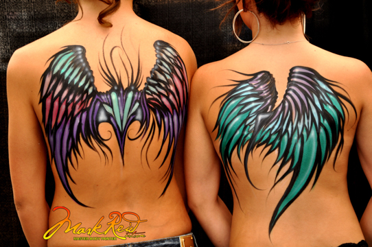the backs of two women with colorful wings painted on them