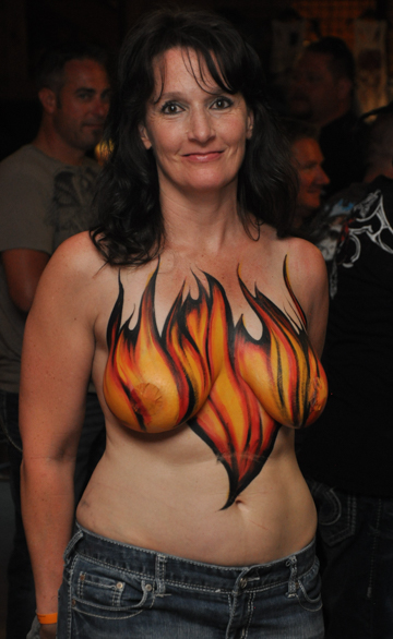 black haired woman with flames painted on her chest