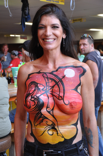 black haired woman with a body painting on her chest of the outline of a woman shooting the moon with a bow and arrow.
