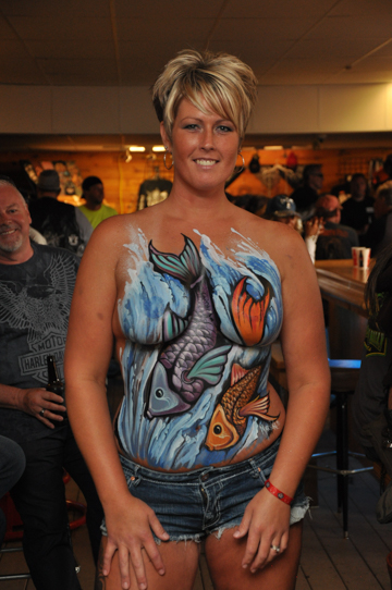 blonde woman with a body painting on her chest of fish jumping