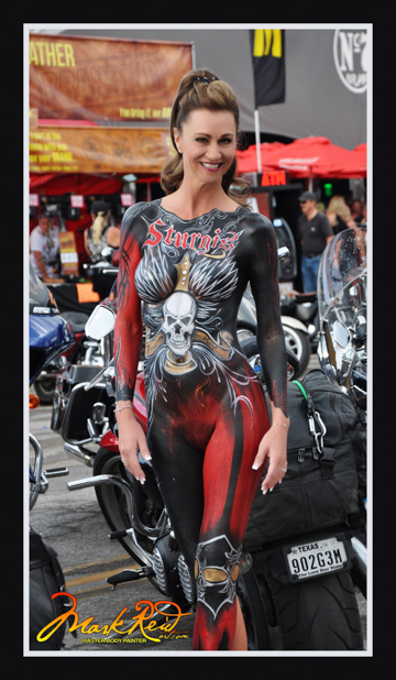 stunning brunette in full body paint that is very intricate painted with red and black backgrounds featuring a skull on her stomach