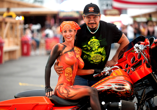Mark Reid with a brunette woman in a full body painting featuring skulls painted in orange that matches the motorcycle she is on
