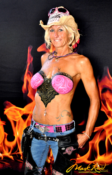 blonde woman in a cowboy hat with intricate pink and black design painted on her chest