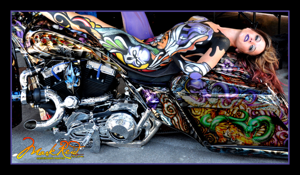 brunette woman with her entire body painted in a very elaborate colorful design that matches the motorcycle she is laying on her back on with her feet on on the handle bars