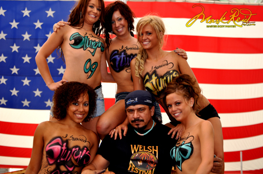 Mark Reid with five models in front of a large american flag