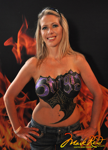 blonde woman with artistic purple and black logo painted on her chest