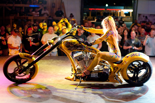 side view of a blonde woman in detailed yellow body paint sitting on a similarly painted motorcycle